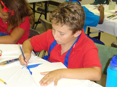 A Community Christian Academy student works on a painting