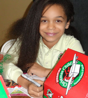 A Community Christian Academy student prepares an Operation Christmas Child shoebox